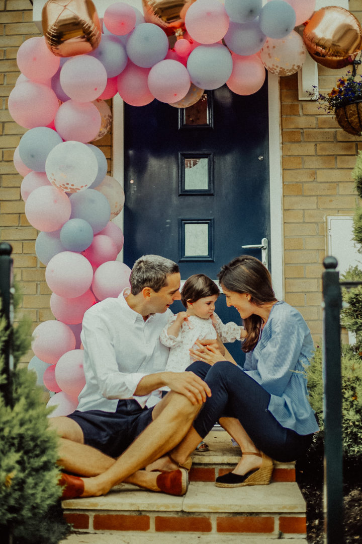 At home doorstep 1st baby girl birthday occasion celebration with mother father parents decoration balloons photography in Shenley, Milton Keynes